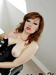 Pretty redhead in black corset and nylons masturbating with her fingers